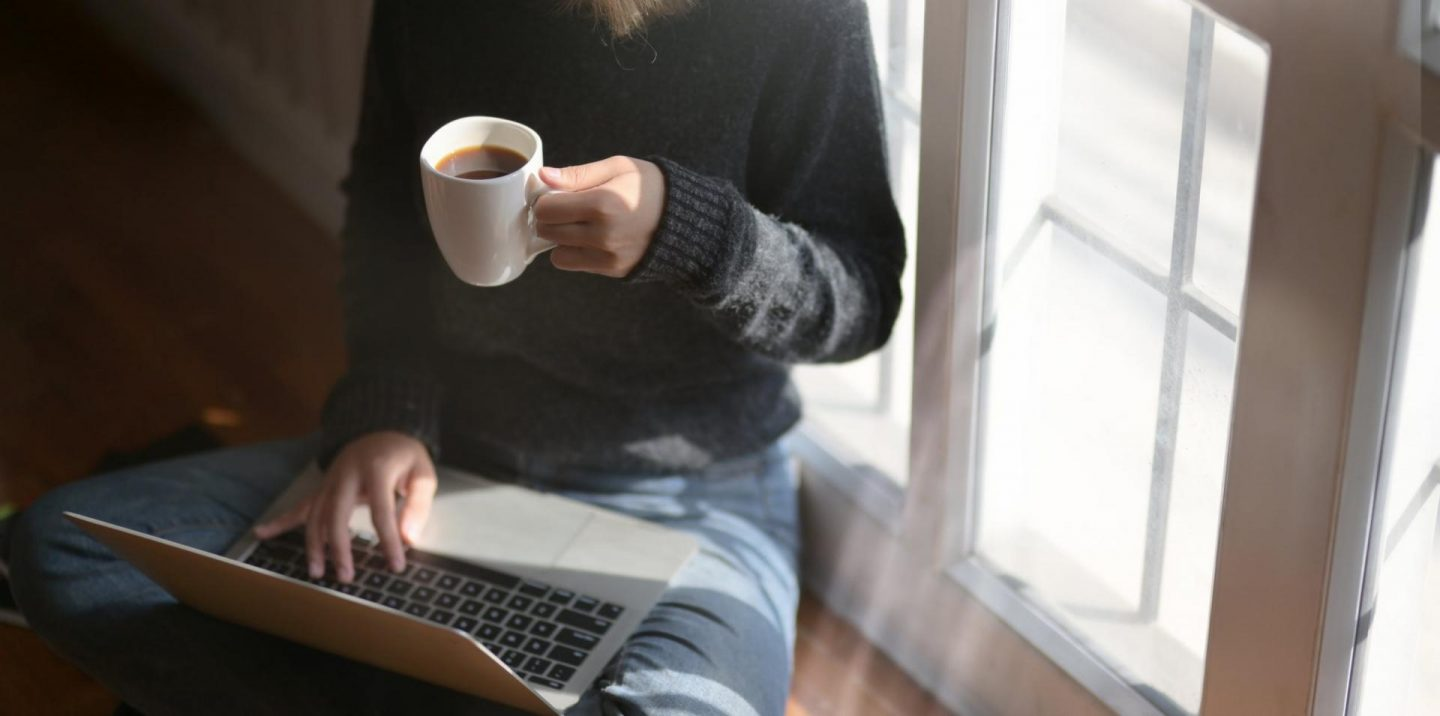 girl on laptop drinking coffee